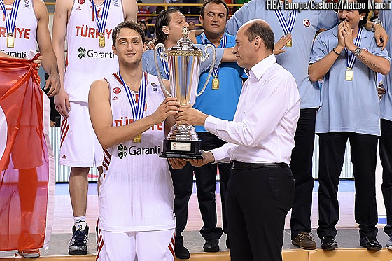 FIBA Europe President Turgay Demirel handing the championship trophy to Turkey's captain Tayfun Erülkü
